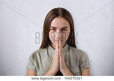 A confident young girl with beautiful dark eyes and hair praying with her hands together on grey background having believe in better future. Concept of mediation and prayer. Praying beautiful woman