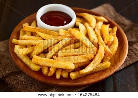 Fresh homemade crispy French fries with a small bowl of ketchup on wooden plate photographed with natural light (Selective Focus Focus one third into the fries)