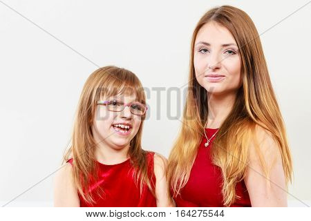 Play and fun. Charming little girl making funny crazy face with joyful mother. Smiling lovely cute female child and woman. Positive facial emotion.