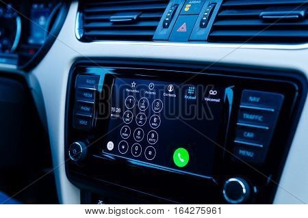 PARIS FRANCE - DEC 13 2016: Apple CarPlay phone main screen in modern car dashboard in blue background tone. CarPlay is an Apple standard that enables a car radio or head unit to be a display and controller for an iPhone