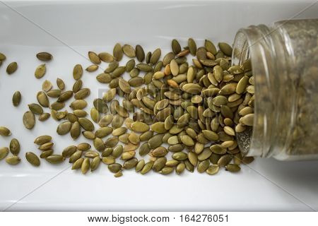 Pumpkin Seeds Spilling Out Of Container, From Above, Close