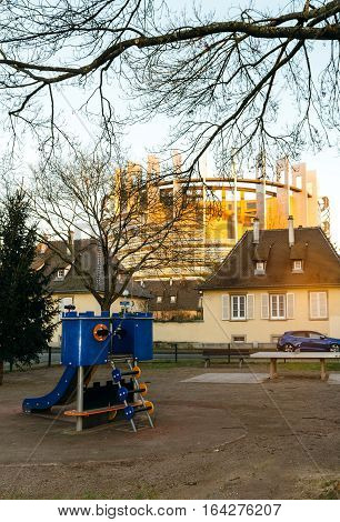 STRASBOURG FRANCE - NOV 29 2016: Kids playground park with European Parliament building in the background - concept for the future of kids in the European union EU UE