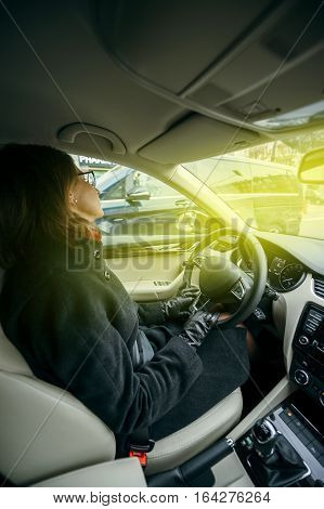 Elegant woman driving confident a car in city enjoying the traffic and good radio station music