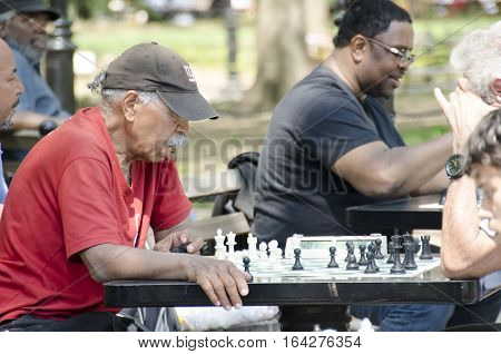 New York City USA - May 4 2015: old man playing chess in Washington square Park in Manhattan