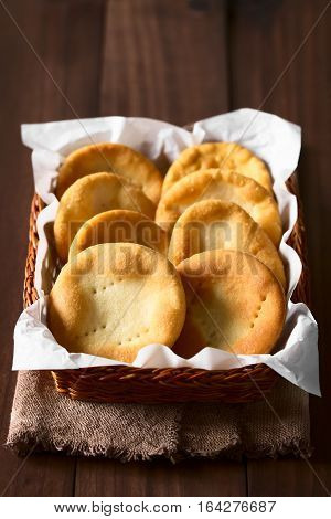 Traditional Chilean Sopaipilla fried pastries made of a bread-like leavened dough served in a basket photographed on dark wood with natural light (Selective Focus Focus on the front of the left and on the right side of the right sopiapillas in the front)