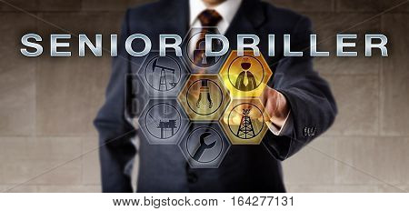 Industrial manager touching SENIOR DRILLER on a virtual control screen. Oil and gas industry career metaphor for a mature supervisory position coordinating the use of drill and rotating equipment.