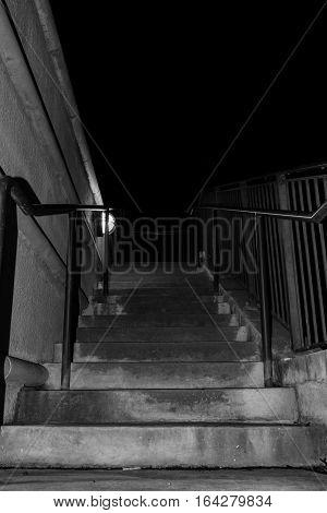Dark stairway dimly lit in black and white.