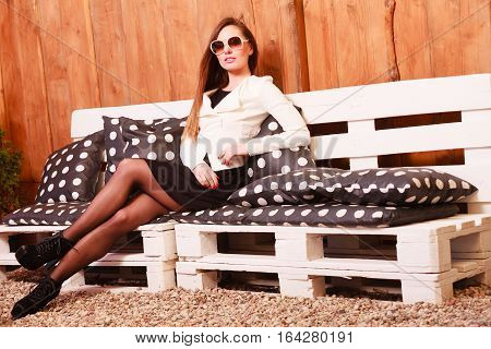 Fashion concept. Young photogenic girl posing on bench. Beautiful woman resting spending free time.