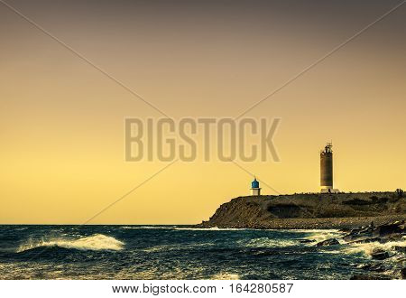 lighthouse and small church at stormy sunset