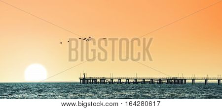 seascape with vivid marine sunset and pier