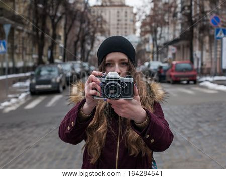 Hipster girl traveler with retro camera taking photo on city street