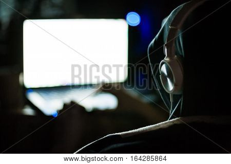 Man hacker in hood and headphones working on laptop in the dark