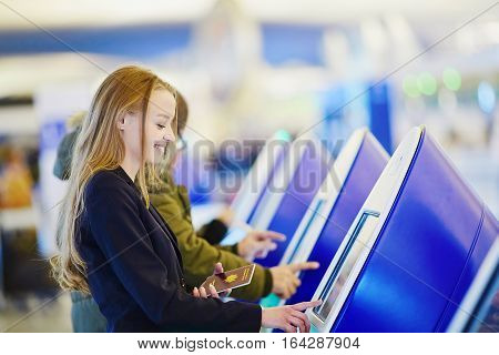 Young Business Woman Doing Self Check-in In International Airport Terminal