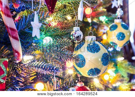 Christmas tree decorations.  Yellow, shiny finish, orb with blue circles, glows, surrounded by bright and vibrant multicolored mini-lights on a small faux indoor Christmas tree.