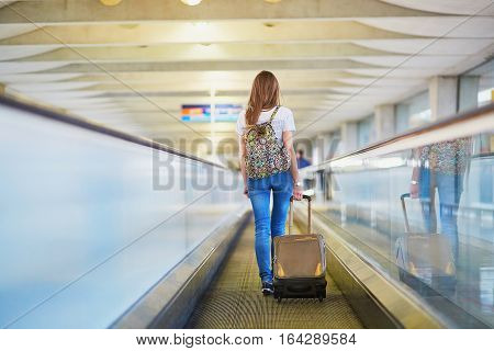 Tourist Girl With Backpack And Carry On Luggage In International Airport, On Travelator