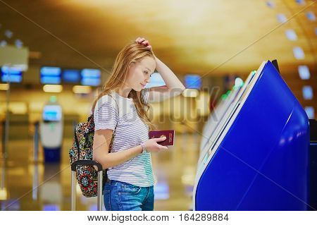 Unhappy Tourist Girl In International Airport, Doing Self Check-in