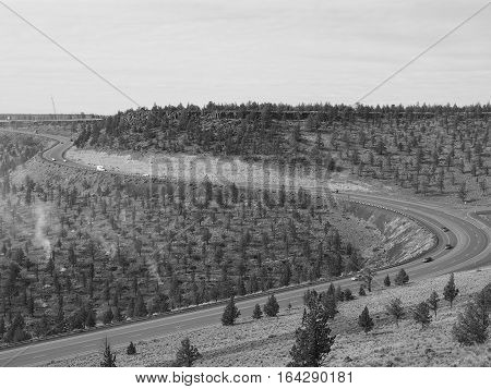 Highway 26 winds down Ochoco Butte into Prineville in Central Oregon with juniper trees and slash burning on a winter day.