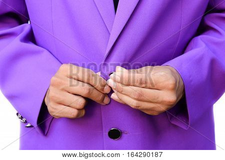 Handsome elegant young fashion man in suit purple with fasten the button on white background