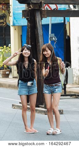 PHUKET THAILAND SEPTEMBER 27: Tourists selfie at the walking street among old building Chino Portuguese style on street of Phuket town Thailand on September 27 2016.