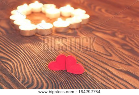 Two valentine hearts burning candles romantic atmosphere. Two Hearts on a wooden board. Valentine's Day. Valentine's Greeting card.