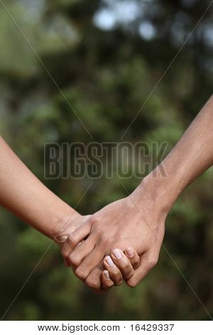 Young couple holding hands (closeup) while outdoors in a park