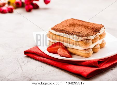 Tiramisu with strawberry on the table. Valentines concept.