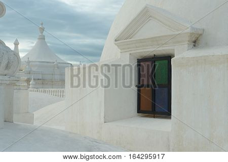Colorful window in cathedral white roof. White roof of central cathedral in Leon city nicaragua