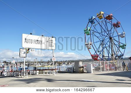 NEWPORT BEACH CALIFORNIA - JANUARY 6 2017: The Balboa Island Ferry and Ferris Wheel. The ferry transports cars and pedestrians from Balboa Island to the Balboa Peninsula and Fun Zone.