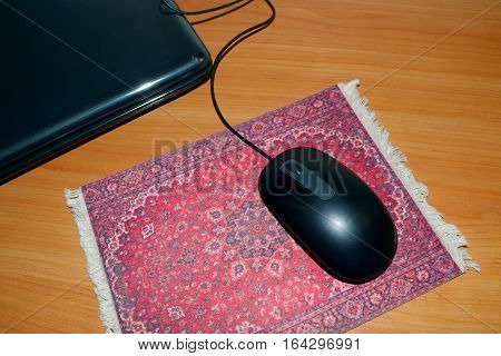 Computer mouse black lies on the Mat on the table.
