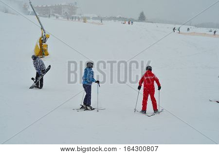 Ski instructor with skiers in ski school on mountain slopes