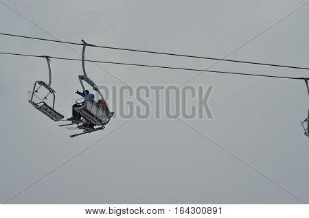 ski lift, chairlift against grey sky background. Winter sport