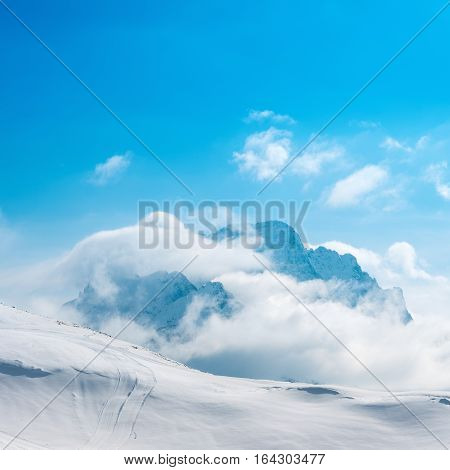 beautiful winter landscape of Dombaj with blue sky clouds and descent from the mountain Russia