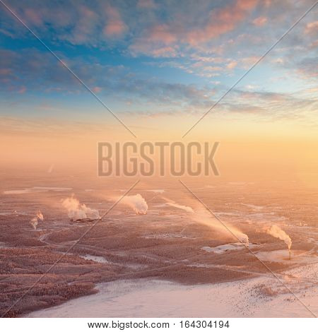 Aerial view of industrial terrain on sundown during frosty winter.