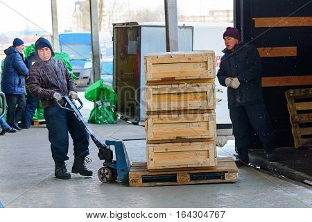 Moscow, Russia - December 13, 2016: Warehouse transport and logistics company. Worker transporting wooden boxes on a hand trolley.