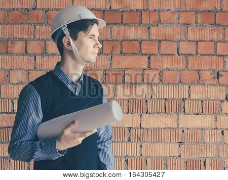 Portrait of the young man engineer with paper