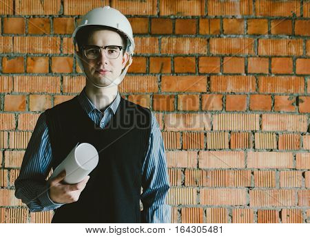 Portrait of the young student engineer in helmet and with paper