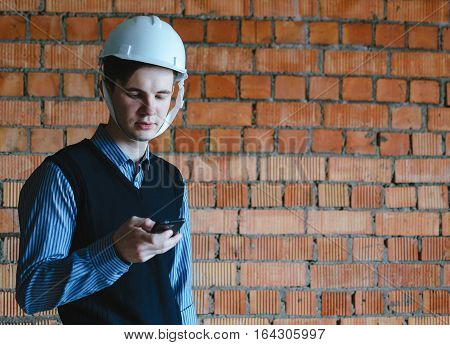 Young man specialist with phone on the orange bricks background