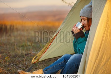 Young beautiful woman in colorful sports wear and trekking shoes sitting in light olive bivouac with metal mug in hands at autumn landscape background with sunset sunlight and mountains at the horizon
