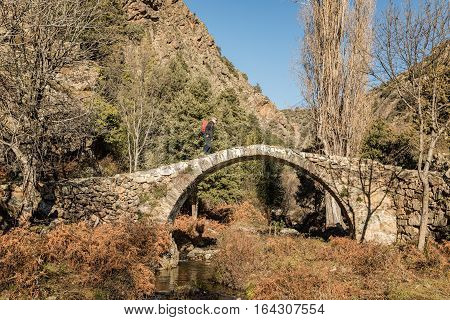 A hiker walks over an ancient stone Genoese bridge crossing a stream in the mountains of the Tartagine valley near Mausoleo in the Balagne region of Corsica