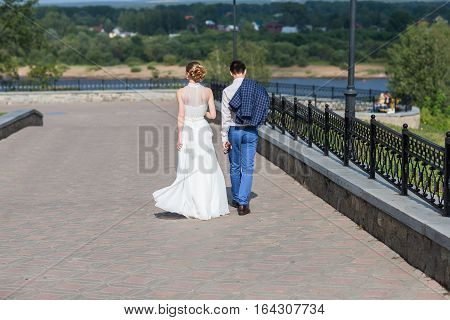 Happy bride and groom celebrating wedding day. Married couple going away on bridge. Long family life road concept.