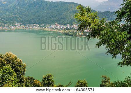 Town on green lake. Pokhara with Lake Phewa in Nepal.
