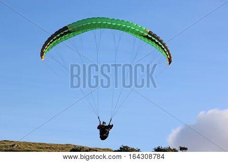 Paraglider flying his wing above Dartmoor, Devon