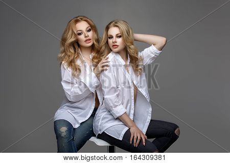 Two beautiful young women with long blond hair and makeup wearing white men shirts and jeans sitting over grey background. Sisters. Studio shot. Copy space.