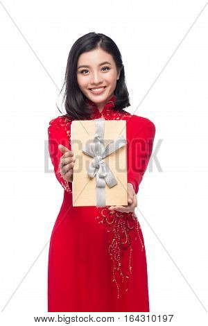 Vietnamese young woman in Ao Dai dress holding gift box.