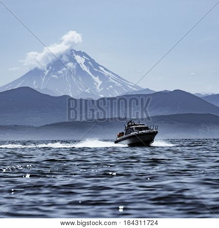The Sunday at noon. Viluchinsky volcano, the sky, the clouds, the bay, the boat.