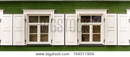 Two windows with open white blinds on an old green wooden house