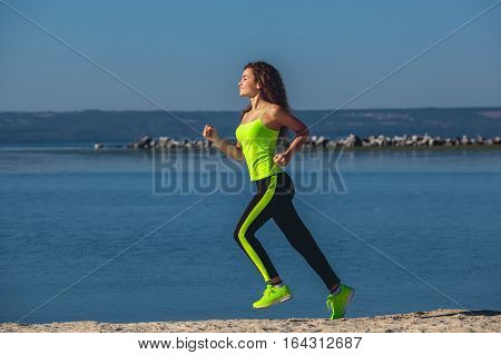 Young athlete with curly hair light green tracksuit and sneakers running on the beach in summer morning exercise. Sports and healthy lifestyle.