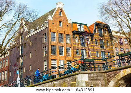 Amsterdam, Netherlands - April 1, 2016: Traditional old buildings and people near bridge in Amsterdam, the Netherlands