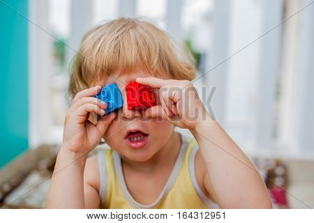 The Boy Makes Eyes Of Colorful Children's Blocks. Cute Little Kid Boy With Glasses Playing With Lots