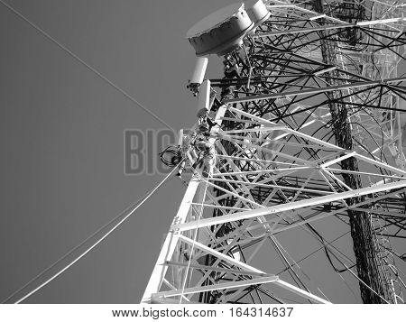 BLACK AND WHITE PHOTO OF TELECOM WORKERS REPAIRING CABLES ON TOWER